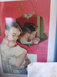 Tilly's father David holding a newborn Tilly. David is a white man with brown hair and glasses and Tilly is wearing a white garment. There is a red wall behind them with a mirror which reflects David.